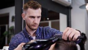 Imagem do barbeiro masculino à moda que usa o hairdryer para fazer o corte de cabelo moderno no barbeiro O homem novo está fundin video estoque