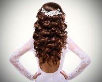 Imagem do cabelo marrom encaracolado longo menina moreno no vestido de casamento branco com um baixo-corte para trás Imagem de Stock