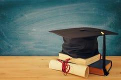 Imagem do chapéu negro da graduação sobre livros velhos ao lado da graduação na mesa de madeira Instrução e de volta ao conceito  imagem de stock