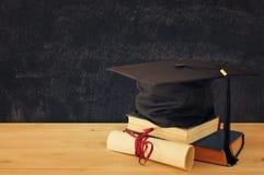 Imagem do chapéu negro da graduação sobre livros velhos ao lado da graduação na mesa de madeira Instrução e de volta ao conceito  imagens de stock