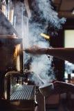 Imagem do close-up do barista fêmea usando a máquina defatura para cozinhar o leite no café fotografia de stock