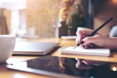Imagem do close up da escrita da mão do ` s da mulher em um caderno vazio com o copo do portátil, da tabuleta e de café na tabela Imagem de Stock