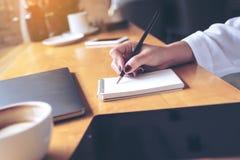 Imagem do close up da escrita da mão do ` s da mulher em um caderno vazio com o copo do portátil, da tabuleta e de café na tabela Fotos de Stock