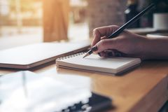 Imagem do close up da escrita da mão do ` s da mulher em um caderno vazio com o copo do portátil, da tabuleta e de café na tabela Imagens de Stock