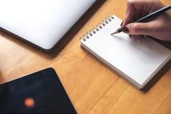 Imagem do close up da escrita da mão do ` s da mulher em um caderno vazio com o copo do portátil, da tabuleta e de café na tabela Fotografia de Stock