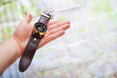 Imagem do close up da mão com compasso magnético sobre um mapa Imagens de Stock Royalty Free