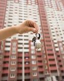 Imagem do close up da mão fêmea que guarda chaves do apartamento novo Casa grande nova no fundo Imagens de Stock Royalty Free