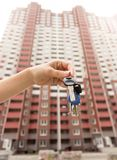 Imagem do close up da mão fêmea que mantém chaves do apartamento novo contra a casa grande sob a construção Foto de Stock