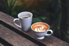 Imagem do close up de dois copos do café preto e do latte com arte do latte do coração no banco de madeira na natureza verde Foto de Stock Royalty Free