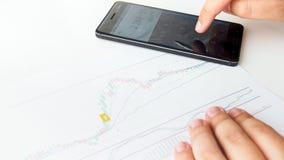 Imagem do close up de riscos calculadores do homem de negócios usando o gráfico financeiro da atividade foto de stock