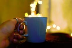 Imagem do close up de uma mão que guarda o copo branco do café quente com fundos do bokeh fotografia de stock royalty free