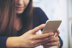 Imagem do close up de uma mulher de negócio asiática bonita com cara do smiley usando e olhando o telefone esperto Foto de Stock Royalty Free
