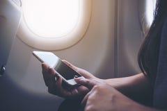 Imagem do close up de uma mulher que guarda e que toca no telefone esperto branco ao lado de uma janela do avião com nuvens e céu foto de stock