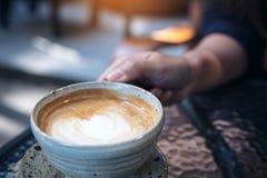 Imagem do close up de uma mulher que guarda uma xícara de café na tabela de vidro imagens de stock