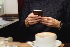 Imagem do close up de uma mulher que realiza e que usa o telefone esperto com o copo de café na tabela de madeira no café foto de stock