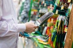 A imagem do close up do homem ou da mulher entrega a seleção ou a escolha para ferramentas de jardinagem de compra como o ancinho Imagens de Stock