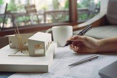Imagem do close up dos arquitetos que tiram o papel de desenho da loja com modelo da arquitetura imagens de stock royalty free
