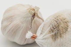 Imagem do close-up dos bulbos secados mostrados com o branco, rede plástica do alho em que são vendidos dentro Fotografia de Stock