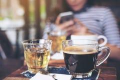 Imagem do close up dos copos do café e do chá quentes na tabela de madeira do vintage no café com a mulher do borrão que usa o te Foto de Stock