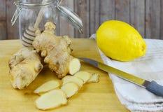 A imagem do close up dos ingredientes para o remédio natural do frio ou da gripe inclui o gengibre, o mel e o limão em um fundo d Fotografia de Stock