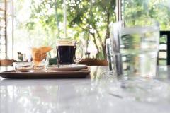 Imagem do close up dos vidros da água e de um copo do café quente com petisco Fotografia de Stock