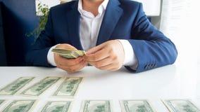 Imagem do close up do homem de negócios bem sucedido que senta-se no escritório e que conta o dinheiro na mesa imagens de stock
