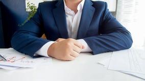 Imagem do close up do homem de negócios no terno azul que senta-se atrás da mesa coberta com os gráficos e as cartas fotos de stock royalty free