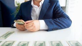 Imagem do close up do homem de negócios que senta-se atrás da mesa e que coloca a pilha de dinheiro na frente dele imagem de stock royalty free