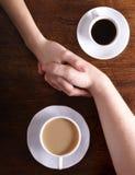 A imagem do conceito de dois lig as mãos e o café Imagens de Stock Royalty Free