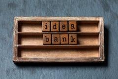 Imagem do conceito do banco da ideia A prateleira do vintage com blocos text letras, caixa de madeira envelhecida Fundo de pedra  imagens de stock