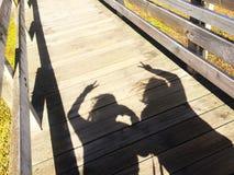 A imagem do conceito do melhor amigo, uma sombra preta de dois povos que mostram a mão da paz assina na maneira de madeira do tra Fotografia de Stock Royalty Free