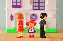 Imagem do conceito do pai ocupada ou irritada e da criança no meio na frente de poucas bonecas plásticas do brinquedo (homem, fêm Foto de Stock Royalty Free