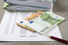 Imagem do conceito do lucro e da perda de uma pena, de uma calculadora e de umas moedas em originais financeiros foto de stock royalty free