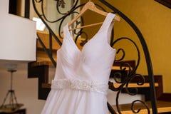 Imagem do corpete de um vestido de casamento branco em um gancho de madeira Fotografia de Stock