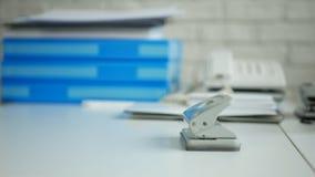 Imagem do escritório da mesa com documentos arquivados e um perfurador de furo de papel na tabela imagens de stock royalty free