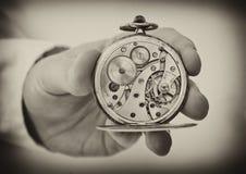 Mão que guardara a mostra antiga do relógio de bolso o mecanismo do maquinismo de relojoaria. fotografia de stock