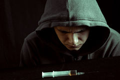 Imagem do Grunge de um viciado em drogas deprimido que olha uma seringa e drogas Foto de Stock Royalty Free
