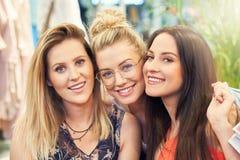 Imagem do grupo de amigos felizes que compram a roupa na alameda fotografia de stock royalty free