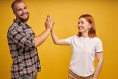 Imagem do homem amigável e da mulher dos jovens na roupa básica que riem e que dão altamente cinco isolada sobre o fundo amarelo imagens de stock