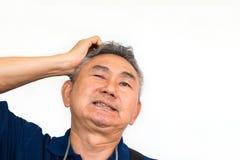 A imagem do homem asiático idoso tem uma dor de cabeça Fotos de Stock Royalty Free