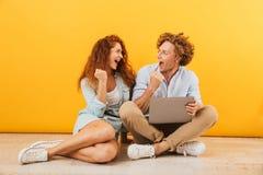 Imagem do homem bonito satisfeito dos pares e da mulher 20s que sentam-se no floo foto de stock