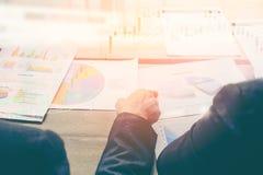 A imagem do homem de negócio dois discute o papel do relatório da carta da venda na tabela imagens de stock royalty free