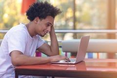 Imagem do homem de negócios afro-americano que trabalha em seu portátil Homem novo considerável em sua mesa foto de stock