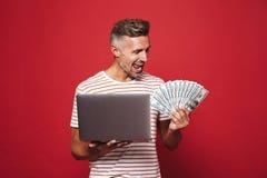 Imagem do homem deleitado em t-shirt listrado que sorri ao guardar foto de stock