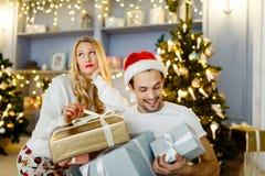 Imagem do homem e da mulher alegres no tampão de Santa com o presente na caixa imagem de stock