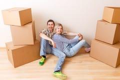 Imagem do homem e da mulher que sentam-se no assoalho entre caixas de cartão imagem de stock royalty free