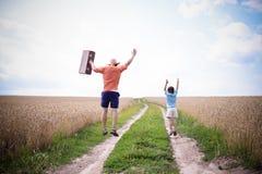Imagem do homem e do menino que saltam na estrada no meio Fotos de Stock