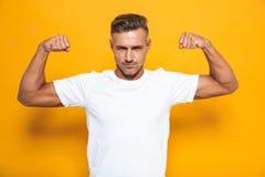 Imagem do homem europeu 30s no t-shirt branco que levanta as mãos e que mostra o bíceps imagens de stock