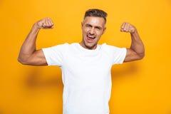 Imagem do homem forte 30s no t-shirt branco que aumenta os braços e que mostra o bíceps fotos de stock
