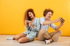 Imagem do homem novo considerável e da mulher encaracolado que sentam-se no CCB do assoalho fotos de stock royalty free